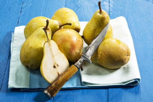 Williams pears and knife on blue wooden table - MAEF007415