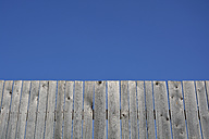 Grey long board fence in front of blue sky - AXF000594