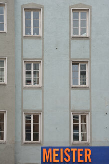 Germany, Bavaria, Munich, part of grey house front with windows and sign - AX000576