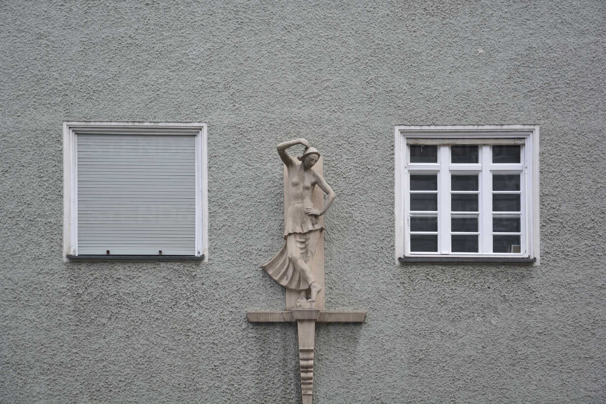 Germany, Bavaria, Munich, part of grey house front with two windows and sculpture - AX000574 - Axel Ganguin/Westend61