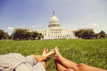 USA, Washington D.C., Couple relaxing in meadow in front of the Capitol - MBEF000899