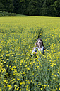 Germany, Bavaria, Starnberg, girl in a rape field - CRF002517