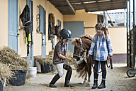 Germany, NRW, Korchenbroich, Boy and Girl at riding stable with mini shetland pony - CLPF000012