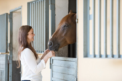 Germany, NRW, Korchenbroich, Young woman feeding horse in stable - CLPF000005