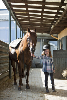 Germany, NRW, Korchenbroich, Little girl with horse in stable - CLPF000001