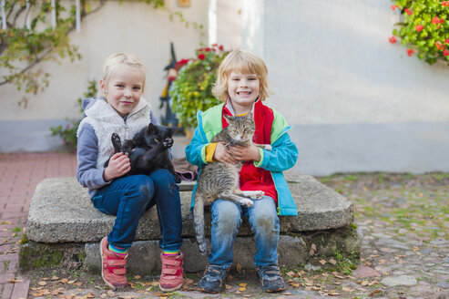 Two children sitting on a stone slab and holding two cats - MJ000426