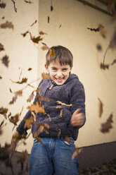 Grinning little boy throwing autumn leaves - MJF000419
