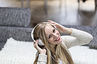 Smiling young woman with headphones - DRF000306