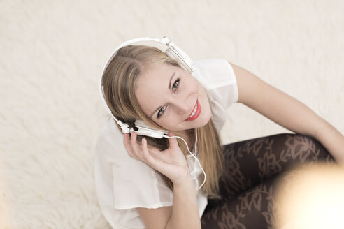 Smiling young woman with headphones sitting on a carpet - DRF000300