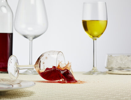 Glass of red wine toppling down on table - AKF000273