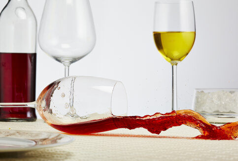 Glass of red wine toppling down on table - AKF000275