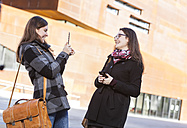 Two young women using digital tablet outdoors - DISF000226
