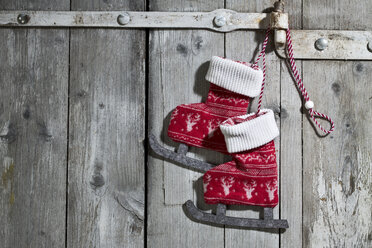 Pair of decorative textile ice skates hanging on wooden door - MAEF007449