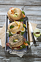Three different bagels garnished with salami, sausage, slices of bacon, rocket salad, lettuce, cucumber carrot, egg, cream cheese and cress and parsley - MAEF007486