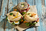 Three different bagels garnished with salami, sausage, slices of bacon, rocket salad, lettuce, cucumber carrot, egg, cream cheese and cress and parsley - MAEF007483