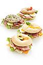 Four different bagels garnished with slices of bacon, lettuce, cucumber, carrot, tomato, Fol Epi, egg, cream cheese and cress and parsley - MAEF007490