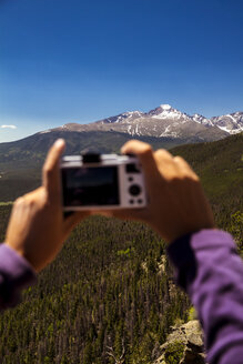 USA, Colorado, Rocky Mountain National Park, Woman taking a picture of Longs Peak and Mount Meeker - MBE000919