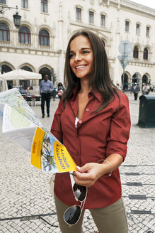 Portugal, Lisboa, Baixa, Rossio, Estacio do Rossio, smiling young woman with city map - BIF000078