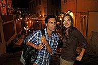 Portugal, Lisboa, Carmo, Calcada du Duque, young couple looking for restaurant at night - BIF000072