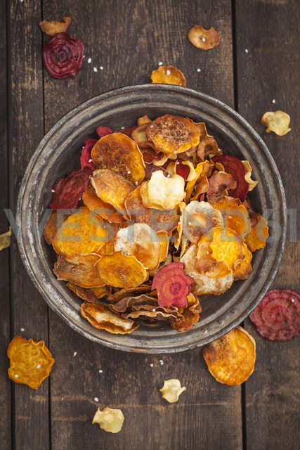 Roasted vegetable chips made of parsnips, sweet potatoes, beetroots, carrots and turnips on plate - ECF000397