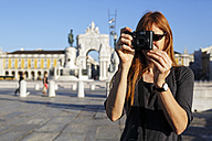 Portugal, Lisboa, Baixa, Praca do Comercio, woman photographing in front of triumphal arch - BIF000084