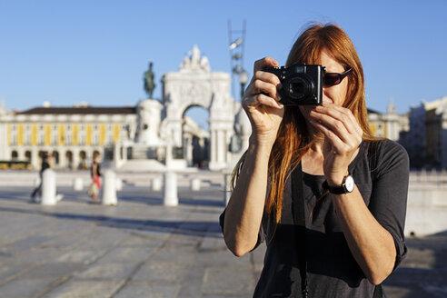 Portugal, Lisboa, Baixa, Praca do Comercio, woman photographing in front of triumphal arch - BIF000084