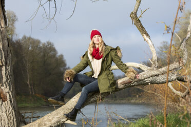 Young woman sitting at tree trunk - MAE007538