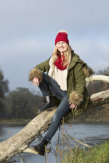 Smiling young woman sitting at tree trunk - MAE007537