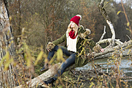 Young woman sitting at tree trunk - MAE007540