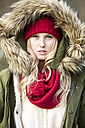 Portrait of young woman wearing woolly hat and hooded jacket - MAE007534