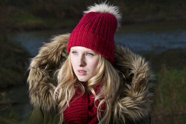 Portrait of smiling young woman wearing red wool cap - MAE007531