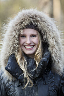 Portrait of smiling young woman wearing hooded jacket - MAE007526