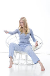 Blond young woman holding remote control in papasan chair - MAEF007555