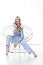Blond young woman holding remote control in papasan chair - MAEF007556