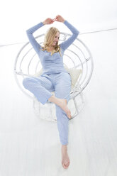 Blond young woman relaxing in papasan chair - MAEF007560