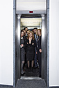 Germany, Neuss, Business people standing in elevator - STKF000794