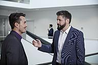 Germany, Neuss, Businessmen talking in corridor - STKF000797