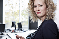 Germany, Neuss, Young business woman using digital tablet - STKF000815