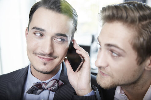 Germany, Neuss, Two young businessmen on the phone - STKF000851