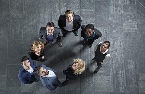 Germany, Neuss, Business people standing on floor, looking up - STKF000771