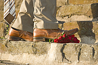 Well-dressed man stepping on red roses - PA000079
