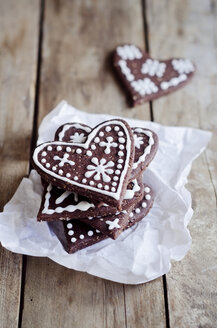 Stack of heart-shaped gingerbread decorated with sugar icing on paper - CZF000121