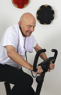 Portrait of old man training on exercise machine - LAF000320