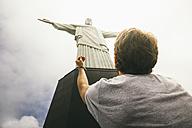 Brazil, Rio de Janeiro, Corcovado, Man praying at Jesus Christ the Redeemer statue - AMCF000014
