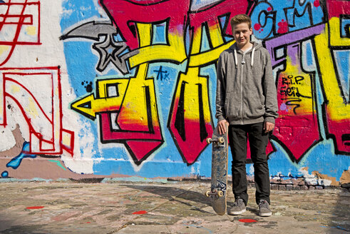 Germany, Cologne, boy with skateboard in front of a graffiti - WG000127