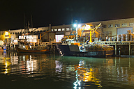 USA, California, San Francisco, Fisherman's Wharf, People unloading commercial fishing boat at night time - ABA001092