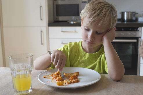 Bored boy sitting at dining table - CRF002535