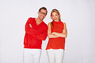 Happy young couple dressed in red and white standing side by side - CHAF000117