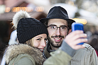 Portrait of smiling young couple photographing themself - DRF000327