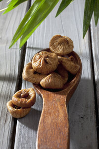 Wooden spoon with dried figs on wooden table - CSF020493